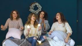 Cztery pięknej dziewczyny tanczą, potrząśnięcie głowy i włosy na łóżku świętuje partyjny slowmotion zbiory