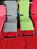 Cztery plażowego krzesła w różnych kolorach na czerwonym chodniku zdjęcia royalty free