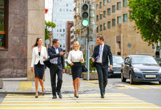 Cztery pomyślnego ludzie biznesu krzyżuje ulicę w mieście Obraz Royalty Free