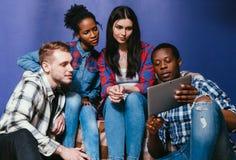 Cztery przyjaciół zegarka koncentrujący wideo na pastylce Zdjęcia Stock
