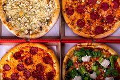 Cztery różna pizza w pudełkach - Caesar, z salami i kurczakiem Odgórny widok obraz stock