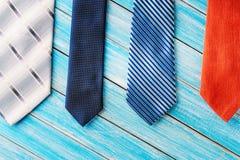 Cztery różnego barwionego krawata w rzędzie na drewnianym błękitnym tle Zdjęcia Royalty Free