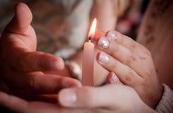 Cztery ręki młodzi ludzie ochrania kruchego świeczki światła ogienia jako metafora opieka i ochrona podczas obrząd religijna obrazy royalty free