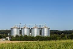 Cztery srebnego silosu w polu pod niebieskim niebem Obrazy Royalty Free
