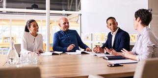 Cztery szczęśliwego ludzie biznesu ono uśmiecha się podczas ich tygodniowy spotykać wpólnie zdjęcie royalty free