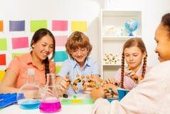 Cztery ucznia studiuje chemię przy sala lekcyjną obraz royalty free