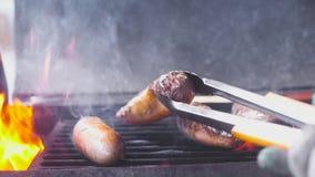 Cztery wieprzowiny wieprzowiny soczystej kiełbasy smażą na gorącym grillu Obracają z forceps Udziały dym i ogień zako?czenie, wol zbiory wideo