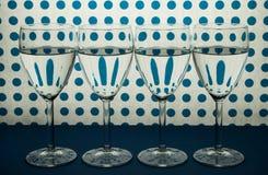 Cztery wina szkła stoi w kreskowym i białym tle z błękitnymi punktami zdjęcie stock