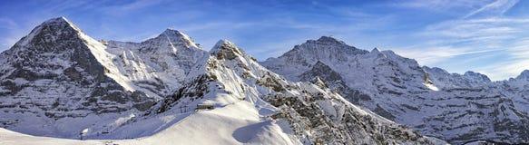 Cztery wysokogórskiego narciarstwa i szczyty uciekają się w szwajcarskich alps Zdjęcie Royalty Free