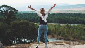 Czuć wolność, szczęście, nikła młodej kobiety pozycja na falezie, cukierki i dźwiganie, ona ręki upwards zbiory wideo