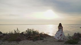 Czuła dziewczyna w długiej pięknej sukni chodzi wzdłuż brzeg rzekiego zbiory wideo