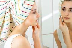 Czuła młoda dziewczyna z ręcznikiem na włosów spojrzeniach w pocieraniach i lustrze twój twarz z bawełnianym dyskiem Fotografia Stock