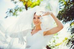 Czuła szczęśliwa panna młoda w przesłonie, szczęśliwa kobieta w ślubnej sukni, biała przesłona zakrywa jej twarz, delikatny i cie zdjęcia stock