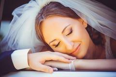 Czuła szczęśliwa panna młoda w samochodzie, szczęśliwa kobieta kłaść jej głowę na ręce mozhchina w ślubnej sukni, biała przesłona zdjęcie royalty free