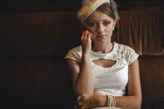 Czuła tajemnicza dama w kapeluszu z przesłoną siedzi na kanapie fotografia stock