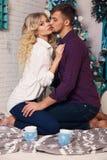 Czuła para w eleganckim odziewa, siedzący obok choinki przy wygodnym domem Zdjęcia Royalty Free
