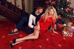 Czuła para w eleganckim odziewa, siedzący obok choinki przy wygodnym domem Obraz Royalty Free