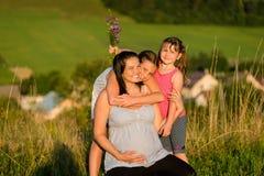 Czule córki ściska szczęśliwej ciężarnej matki outdoors obrazy royalty free