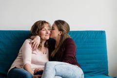 Czule nastoletnia córka całuje jej kochającej matki zdjęcie stock