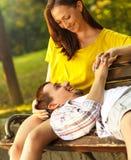 Czule potomstwo pary obsiadanie w parku fotografia royalty free