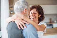 Czule starsza para w miłości stoi indoors w domu, ściskający fotografia royalty free
