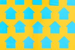Czyści błękitnych majcherów w postaci domów na jaskrawym żółtym tle Jaskrawy układ Egzamin próbny Up Fotografia Royalty Free