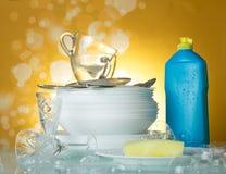 Czyści naczynia, filiżanki, dishwashing detergent i gąbka na kolorze żółtym w mydlanych bąblach, obrazy stock