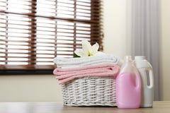 Czyści ręczniki z lelują w koszu i detergenty na stole indoors zdjęcia stock