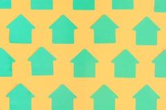 Czyści zielonych majcherów w postaci domów na jaskrawym pomarańczowym tle Jaskrawy układ Egzamin próbny Up Obrazy Royalty Free