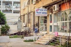 Czynszowy budynek mieszkaniowy z krawiectwo naprawami podpisuje wewnątrz rosjanina i hebrajszczyznę Zdjęcia Royalty Free