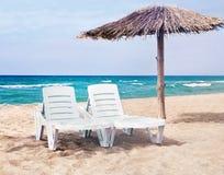Czysta morze plaża z dwa plażowymi łóżkami i plażowym parasolem Obraz Stock