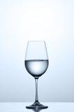 Czysta woda w niezmiennym wineglass podczas gdy stojący na czystym szkle przeciw lekkiemu tłu zdjęcia royalty free