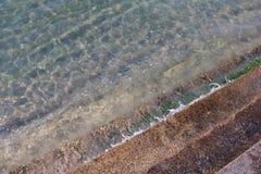 Czystej wody fala z cementowymi schodkami, kryształ - jasny denny nawadnia i wyborowi czyści, Widzią skały na dnie denny natura o Zdjęcie Stock