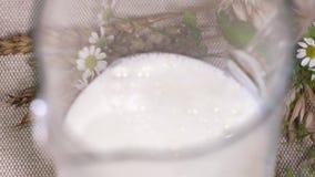 Czysty mleko nalewa w szklanego dzbanek w sznurku, robi pluśnięciom zbiory wideo