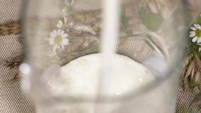 Czysty mleko nalewa w szklanego słój w spout, robi pluśnięciom zdjęcie wideo