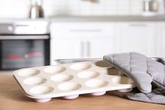 Czysty pieczenia naczynie, słodka bułeczka niecka i piekarnik rękawiczka na stole w kuchni, fotografia stock