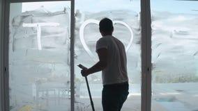 Czysty pracownika writing kocham ciebie na mydlanym nadokiennym szkle podczas cleaning zdjęcie wideo