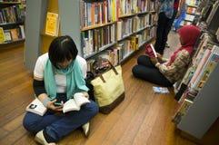 Czytać przy Książkowym sklepem Obrazy Stock
