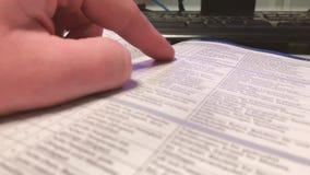 Czyta wewnątrz techniczną książkę przy miejsce pracy w górę zbiory wideo