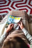 czytający IKEA Kataloguje na leżance zakrywającej z blacnket Zdjęcia Stock
