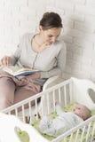 Czytający książkę wyrównującą w kołysce Fotografia Stock
