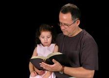 czytanie biblii ojca. Obrazy Stock