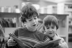 czytanie książki brata. Obrazy Royalty Free