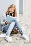 Czytanie studencka książka na zewnątrz szkolnych potomstw fotografia stock