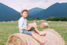 Czytelnicza chłopiec siedzi nad haystack rolką na halnym polu Obraz Royalty Free