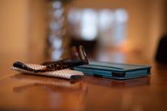 Czytelniczy szkła i ich skrzynki obsiadanie na górze elektronicznej reader/pastylki na drewnianym stole obraz stock