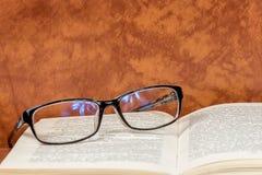Czytelniczy szkła są na otwartej książce zdjęcia royalty free
