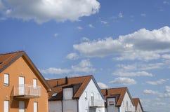 Dächer von Häusern unter blauem Himmel mit Wolken Lizenzfreie Stockbilder