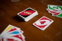 Däck av modiga kort för Uno spridda över hela på en tabell Amerikanskt kortspel arkivfoto