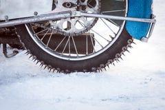 Däcket av motocrossen cyklar på is och snöar på bakgrund, Arkivbilder